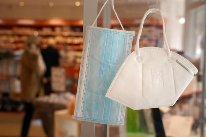 A surgical mask and an N95 mask hang on display for sale at a pharmacy. Photo by Sean Gallup/Getty Images.